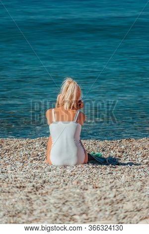 Charming Blonde Girl With Well-shaped Body In White Bikini Sitting On Pebble Beach, And Admiring Fas