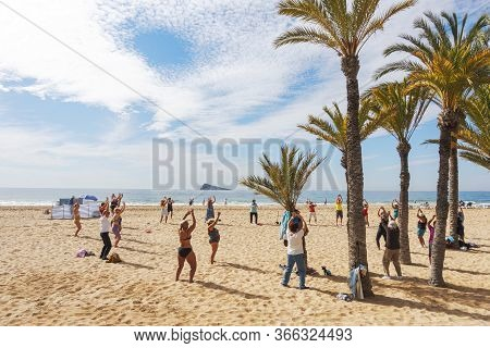 Benidorm, Spain - February 25, 2020: Active Senior People Doing Sport Exercises On The Beach. Health