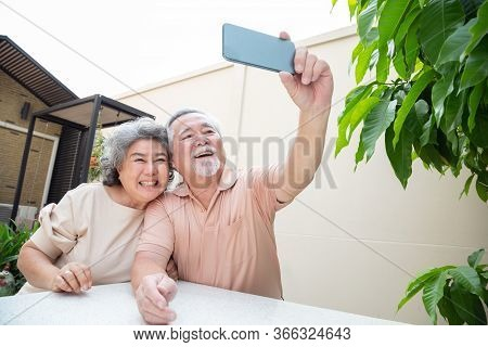 Asian Senior Couple Talking In Video Call Chat On Mobile Phone Or Taking A Selfie, Smart Technology