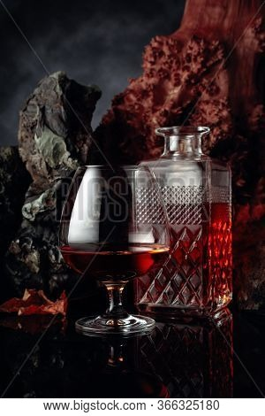 Snifter And Decanter Of Brandy On A Black Reflective Background. In The Background There Are Stones