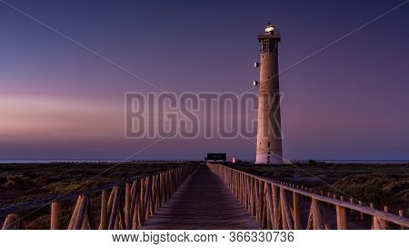 Lighthouse In The Light Of The Blue Hour Shortly Before Sunrise. In The Foreground A Wooden Footbrid