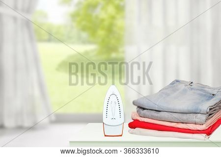 Household Laundry Ironing. Close-up Of A Red Electrical Iron And A Stack Of Ironed Clothes On White