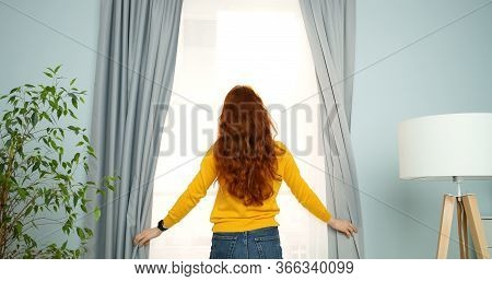 Rear Of Young Woman With Long Red Curly Hair Standing In Living Room At Window And Opening Curtains
