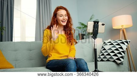 Portrait Of Young Female Blogger Sitting On Couch And Talking In Front Of Smartphone Webcam. Girl Co