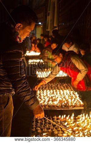 Kathmandu, Nepal - December 06, 2014: Pilgrims At Boudhanath Stupa Lighting Up Butter Candles For Fu