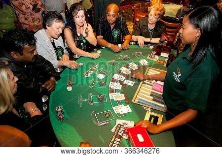 Diverse People Playing Blackjack Card Game At Casino Table