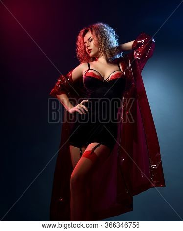 Blonde Curly Woman Is Sexy Posing In Red And Black Lace Sexy Lingerie, Stockings And Transparent Coa