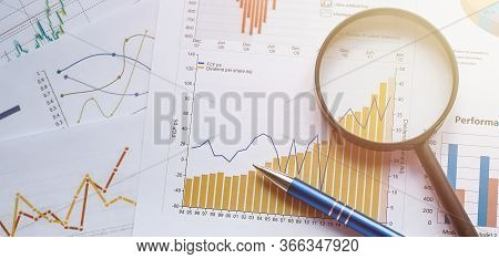 Business Concept With Pencil And Magnifying Glass On Documents. Business Grafs And Charts