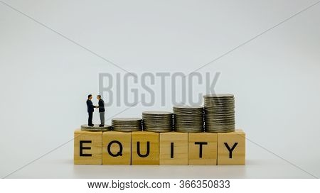 Closeup Of Stack Of Silver Coins And Miniature Figure Two Businessman On Top Of Wooden Block Word Eq