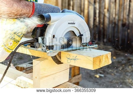 Manual Circular Circular Saw On Wood Metabo. A Man At A Construction Site Saws A Wooden Board Bar Cl