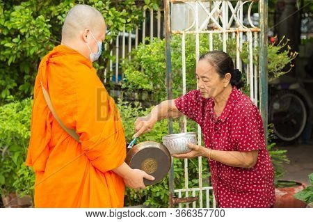 Nonthaburi, Thailand- May 08, 2020 : An Old Asian Woman Is Offering Food To Monks, At Front Home In