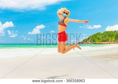Woman In Bikini Jumping On Seashore Of Anse Kerlan Seychelles, With Surgical Mask During Covid-19. P