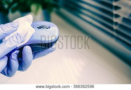 office sanitizing wipe wiping mouse and mousepad with disinfecting wipes. Coronavirus COVID-19 sanitize cleaning disinfection of work desk.