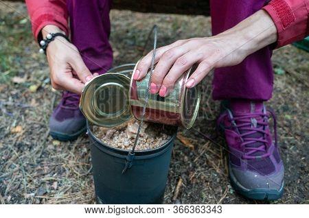The Girl Puts The Stew In A Pot Of Buckwheat Porridge During A Halt.