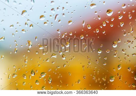 Raindrops On Windshield Of Car. Bright Building Reflected In Raindrops On Glass. Abstract Background