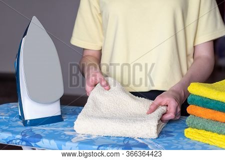 Hands Fold A Ironed Towel, A Modern Iron With A Steam Ironing System, A Clean, Stack Of Ironed Thing