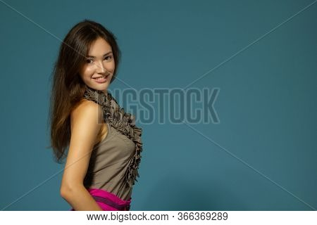 Beautiful cheerful teen girl, studio shot over blue background. Young pretty happy smiling woman. Charming girl with long brown hair looking at camera