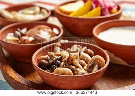 Snack assortment on wooden tray side view. Variety of pickled mushrooms with potato and onion. Served restaurant appetizers in brown pottery bowls. Culinary art. Food portions. Cafe serving