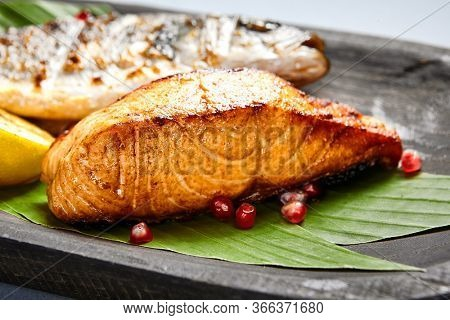 Fish served on wooden rustic plate. Grilled seabass and salmon piece on plant leaves sprinkled with pomegranate seeds. Decorated restaurant meal. Fancy seafood assortment dish. Art of cooking
