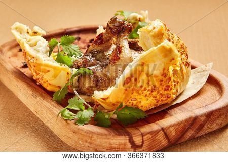 Chicken in dough served on wooden tray. Baked poultry in bread bun. Luxury restaurant food portion. Fancy meal course decorated with parsley. Food presentation art