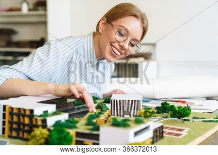 Photo of joyful young woman architect in eyeglasses designing draft with house model and sitting at workplace