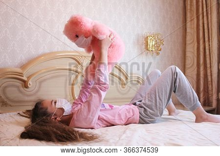 A Girl In A Face Mask Plays With A Pink Teddy Bear In A Face Mask. The Girl Is Lying On The Bed And