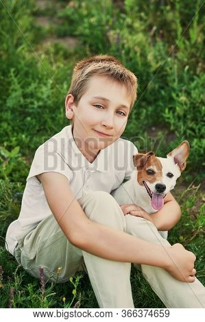 Children's Day. Happy Little Child Boy Having Fun With Dog Pet Jack Russell Terrier On Field. Summer