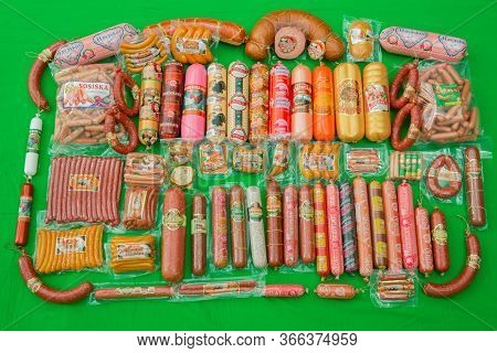 Many Ham Sausage Package Isolated On Green Background . Group Of Whole Tasty Boiled Sausages . A Lot