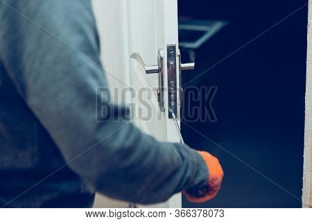 Handyman Repair The Door Lock In The Room. Man Fixing Lock With Screwdriver, Close-up Of Repairing D