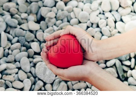 Red Heart In Childrens Hands On Stone Beach Background, Concept Of Love. Symbol Of Love And Family.