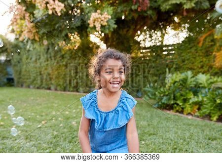 Young Hispanic Girl Chasing And Catching Bubbles In Garden