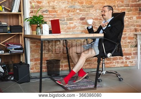 Conference. Young Man Without Pants But In Jacket Working On A Computer, Laptop. Remote Office Durin