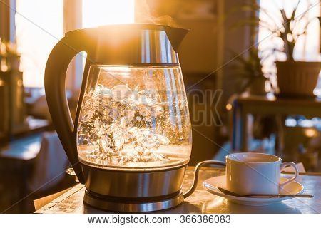 A Transparent Kettle Of Water Boils Against The Background Of The Sunset Shining Through The Window.