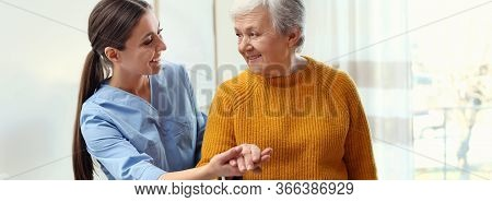 Care Worker Helping Elderly Woman To Walk In Geriatric Hospice. Banner Design