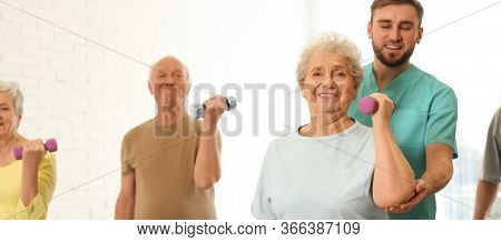 Care Worker Helping Elderly Woman To Do Exercise With Dumbbell In Hospital Gym. Banner Design