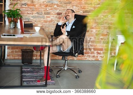 Delighted. Young Man Without Pants But In Jacket Working On A Computer, Laptop. Remote Office During