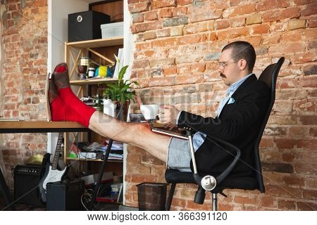 Scrolling. Young Man Without Pants But In Jacket Working On A Computer, Laptop. Remote Office During