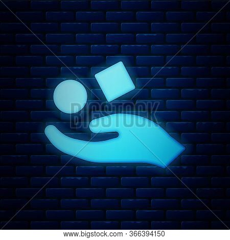 Glowing Neon Cube Levitating Above Hand Icon Isolated On Brick Wall Background. Levitation Symbol