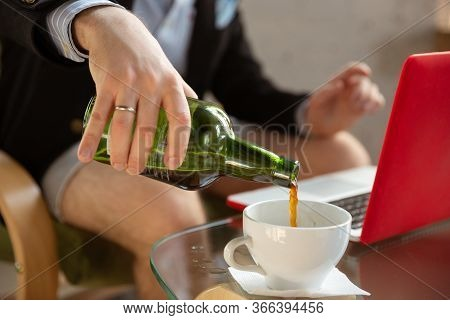 Pours Alcohole. Young Man Without Pants But In Jacket Working On A Computer, Laptop. Remote Office D