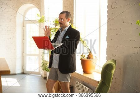 Meeting Online. Young Man Without Pants But In Jacket Working On A Computer, Laptop. Remote Office D