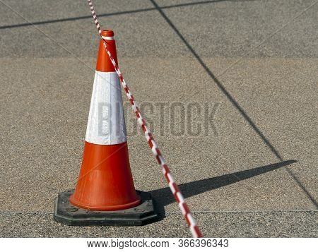 Close-up Of A Red And White Striped Traffic Cone With Barricade Tape On The Road In Sunlight