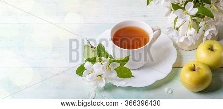 White Cup Of Tea On Shaped Saucer With Blossoming Apple Tree Branches And Two Yellow Apples On Woode