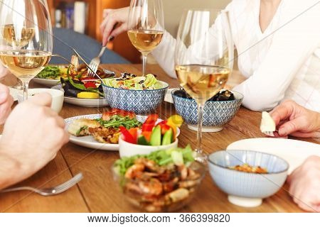 Group Of Anonymous People Eating Healthy Food And Enjoying Wine While Sitting At Table During Dinner