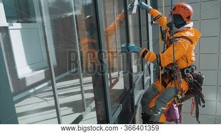 Glazing, A Young Equipped Industrial Climber In An Orange Jumpsuit And Helmet Neatly Washes The Wind