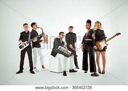 Multiracial Music Band On A White Background. A Group Of International Musicians Rehearsing A Concer