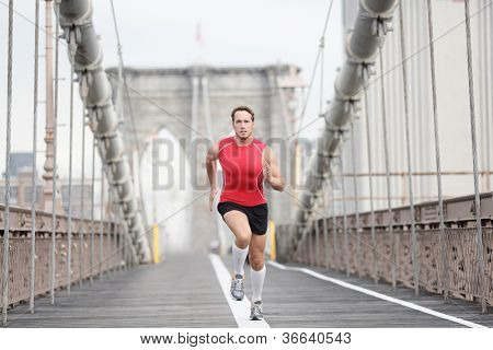 Running runner man sprinting at speed. Male athlete training alone in full body wearing red compression top and socks during run on Brooklyn Bridge, New York City, USA.