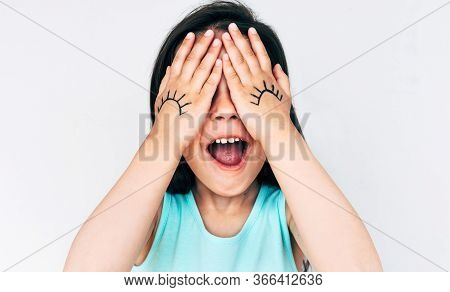 Closeup Portrait Of Little Girl Makes Grimace With Open Mouth, Covers Her Eyes With Both Hands With