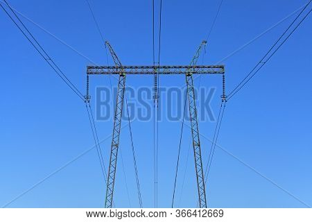 Electric Wires Against The Blue Sky. High Voltage Powerline Tower. Electricity Transmission Pylon. H