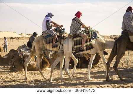 Group Of Tourists Riding Over Dromedary Camel Walking In The Sands Of Sahara Desert, Tunisia, North