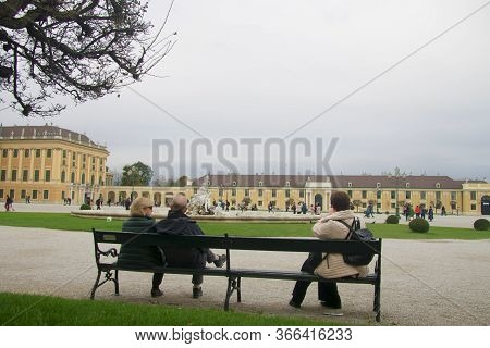 People Sitting On The Bench And Looking To Shonbrunn Palace And Fontain Vienna Austria 03 November 2
